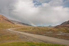 Regnbåge i ett moln som hänger över den lantliga vägen mellan de steniga bergen Arkivbild