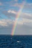 Regnbåge över blå havslodlinje Fotografering för Bildbyråer