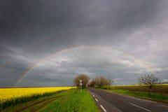 Regnbåge över vägen Arkivbild