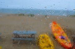 Regndroppar dryper ner fönster av strandkojan Royaltyfri Bild