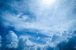 Regndroppar med bakgrund för blå himmel arkivfoto