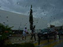 Regndroppar och en suddig bakgrund med folk och bilar arkivbild