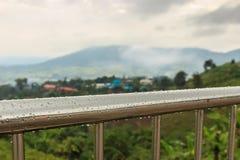 Regndroppar på balkongmetallbalustraden royaltyfri fotografi