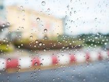Regndroppar på bilexponeringsglas med oskarp vandringsled- och byggnadsbakgrund Royaltyfri Foto