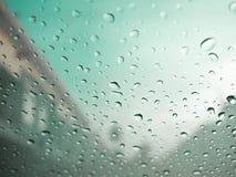 Regndroppar på bils exponeringsglas med oskarp molnig himmel i by Gree Royaltyfri Fotografi