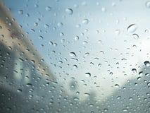 Regndroppar på bils exponeringsglas med oskarp molnig himmel och byn Royaltyfria Bilder