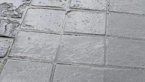 Regndroppar på den stenlade gatan lager videofilmer