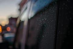 Regndroppar på en svart bil på det bakre svarta fönstret för sida fotografering för bildbyråer
