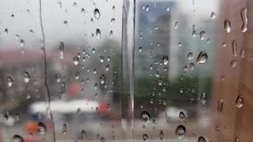 Regndroppar på ett exponeringsglasfönster förser med rutor