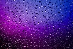 Regndroppar på ett fönster förser med rutor Arkivfoto