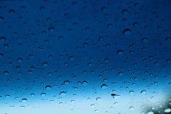 Regndroppar på exponeringsglas, abstrakt bakgrund Arkivfoton