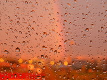 Regndroppar på exponeringsglas Bakgrundsregnbåge och solnedgången Arkivfoto