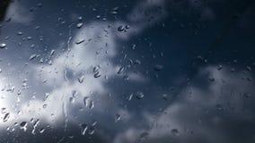 Regndroppar på exponeringsglas och suddig blå himmel och moln royaltyfria foton