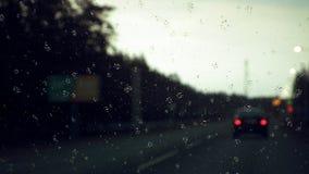 Regndroppar på exponeringsglaset mot bakgrunden av cityscapen arkivbilder