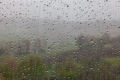Regndroppar på fönster förser med rutor arkivfoton