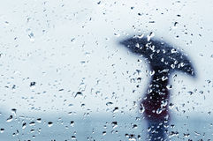 Regndroppar på fönster med personen med paraplyet Arkivbild