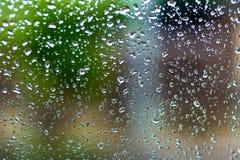 Regndroppar på fönsterexponeringsglas med suddighetsbakgrund royaltyfri foto