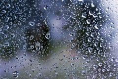 Regndroppar på fönsterexponeringsglas ytbehandlar med molnig bakgrund arkivbild