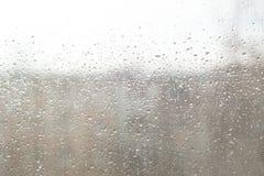 Regndroppar på fönsterexponeringsglas ytbehandlar med molnig bakgrund Naturlig modell av regndroppar royaltyfria bilder
