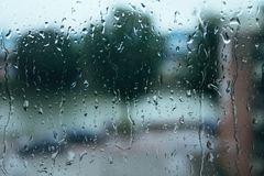 Regndroppar på fönsterexponeringsglaset Arkivfoton