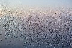 Regndroppar på Glass bakgrund Modellen av vatten tappar efter hällregn, sikt från inomhus Våt textur för abstrakt begrepp Genomsk Arkivfoto