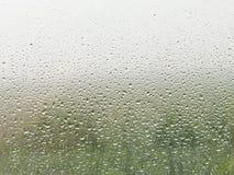 Regndroppar på hem- fönster förser med rutor Arkivbild