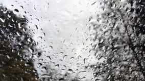 Regndroppar på vindrutan av ett medel Arkivfoto