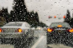 Regndroppar på vindrutan på en regnig dag; bilar stoppade på en trafikljus i bakgrunden; Kalifornien royaltyfri foto
