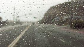 Regndroppar på vindrutan, medan köra ner huvudvägen arkivfilmer