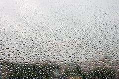 Regndroppar på yttersida för fönsterexponeringsglas fotografering för bildbyråer