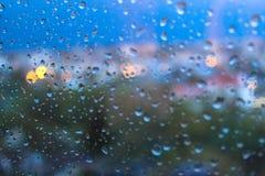Regndroppar på yttersida för fönsterexponeringsglas arkivfoto