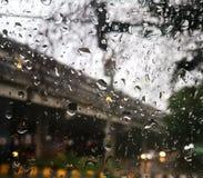 Regndroppar på yttersidan av det reflekterande ljuset för bilspegel in i små små droppar royaltyfria foton