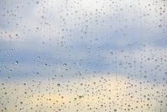 Regndroppar på ett fönster med blå himmel i bakgrunden Royaltyfri Bild