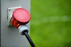 Regndroppar ses på den industriella elektriska proppen under regn Fotografering för Bildbyråer