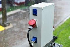 Regndroppar ses på den industriella elektriska proppen under regn Arkivbild
