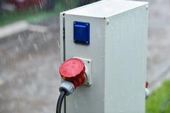 Regndroppar ses på den industriella elektriska proppen under regn Arkivfoto