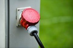 Regndroppar ses på den industriella elektriska proppen under regn Royaltyfri Fotografi