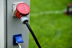 Regndroppar ses på den industriella elektriska proppen under regn Royaltyfria Foton