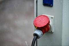 Regndroppar ses på den industriella elektriska proppen under regn Arkivbilder