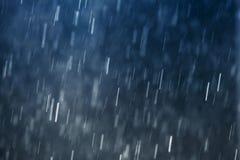 Regndroppar som faller mot mörker - blå bakgrund, långsam slutarehastighet Royaltyfri Foto