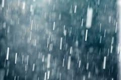 Regndroppar som faller mot mörker - blå bakgrund, långsam slutarehastighet Arkivbild