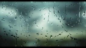 Regndroppar, som faller på ett dimmigt fönster under dagen, då det regnar, och bakgrunden göras suddig arkivfilmer