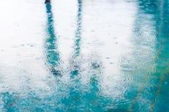 Regndroppar vinkar blured sorl i en pöl med ljust och sh royaltyfri fotografi