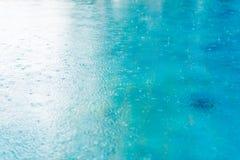 Regndroppar vinkar blured sorl i en pöl med ljust och sh royaltyfri foto
