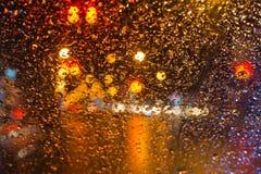 Regndroppe med färgrika trafikljus för gata på bakgrund för abstrakt begrepp för nattsuddighetsbokeh Arkivbilder