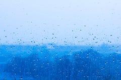 Regndroppe på blått exponeringsglas Arkivbild
