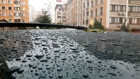 Regndroppe på taket av den svarta bilen som parkeras på vägen Regna dag stock video