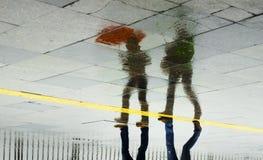 Regnen Sie die Frauen des Reflexionsregenschirmes zwei, die in den Regen gehen Lizenzfreie Stockfotos