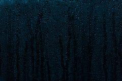 Regnen Sie die Tröpfchen, die hinunter ein Fenster, abstrakter Hintergrund laufen stockbild