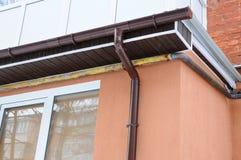 Regnen Sie Gosse auf dem Dach des Balkons Neue Gossen für Wasserentwässerung vom Dach SCHLÜCKCHEN-Plattenhausbau Stockbilder